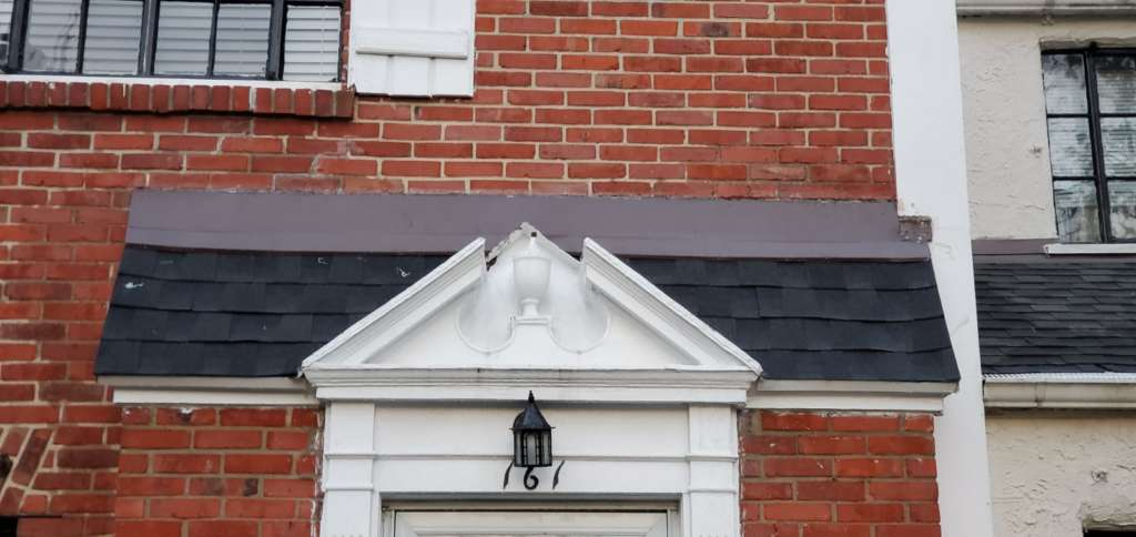 Ripped Shingle Above Entrance After